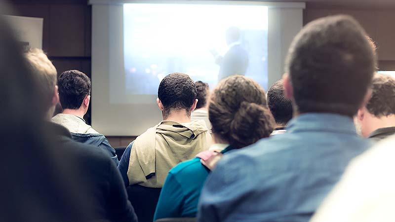Back view of people in a meeting, looking at a presentation on a screen.