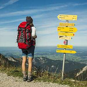 Young woman trekking in Austria, near signposts