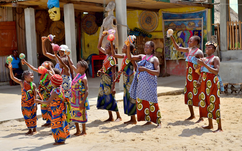 A group of african women and little girls dancing