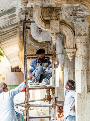 Workers repairing the facade of the City Palace in Udaipur, India