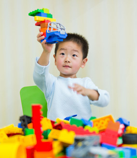 Young boy playing with Lego blocks