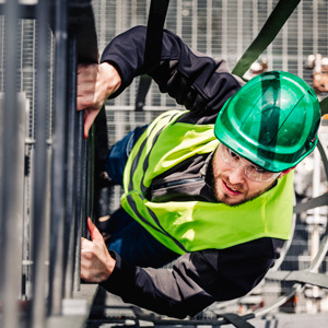 Young male technician, wearing a safety helmet, is climbing a ladder