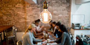 Group of business people brainstorming at a creative office and a light bulb in the foreground.