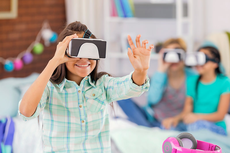 Girls using virtual reality goggles during a party