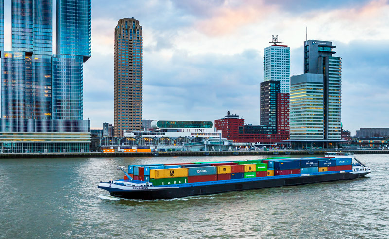 Huge container ship full of freight boxes cruising the river with Rotterdams skyline in the background.