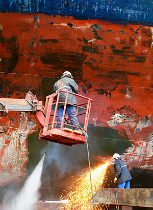Wet scraping process made with high pressure water to clean the surface of the ship before the painting process.