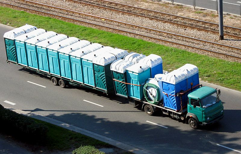 Truck driving with range of portable toilets.