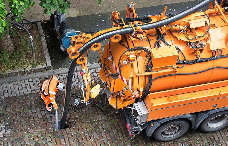 In the street, a worker cleaning a sewer with a vacuum truck, in Germany.