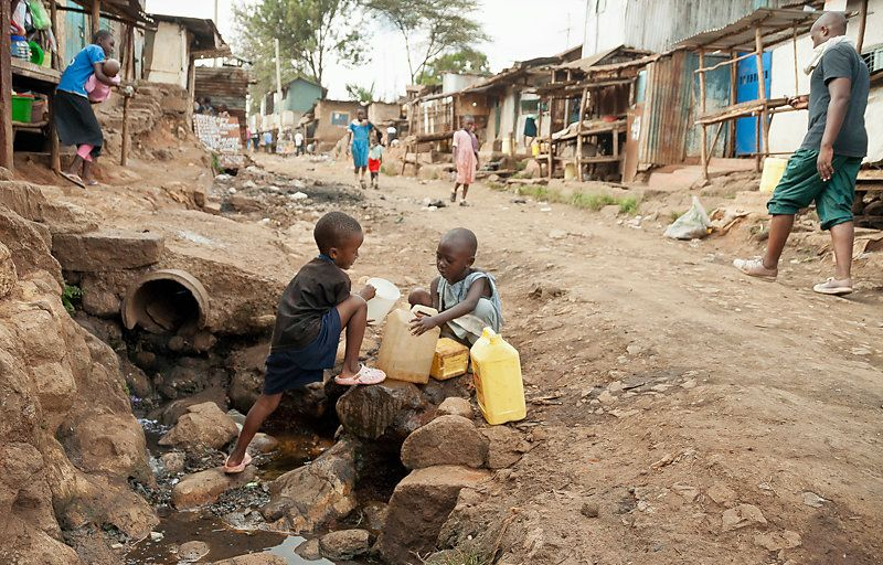 Two little boys in the street are pouring water form the river in cans, in Nairobi, Kenya.