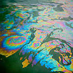Colorful patterns in an oil spill on polluted water.