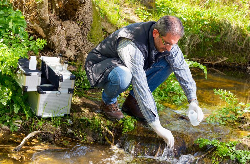 A biologist takes a water sample in a river