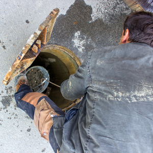 A worker cleaning a sewer.