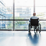 Senior Man in Wheelchair looking out of a window in a hospital corridor.