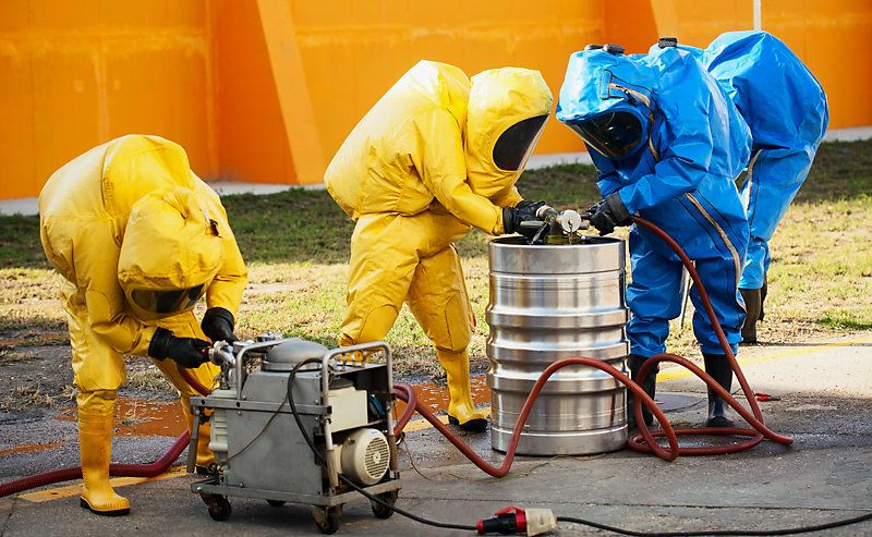 A team wearing hazmat suits and handling hazardous materials.