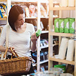A woman is grocery shopping and reading product information on a label.