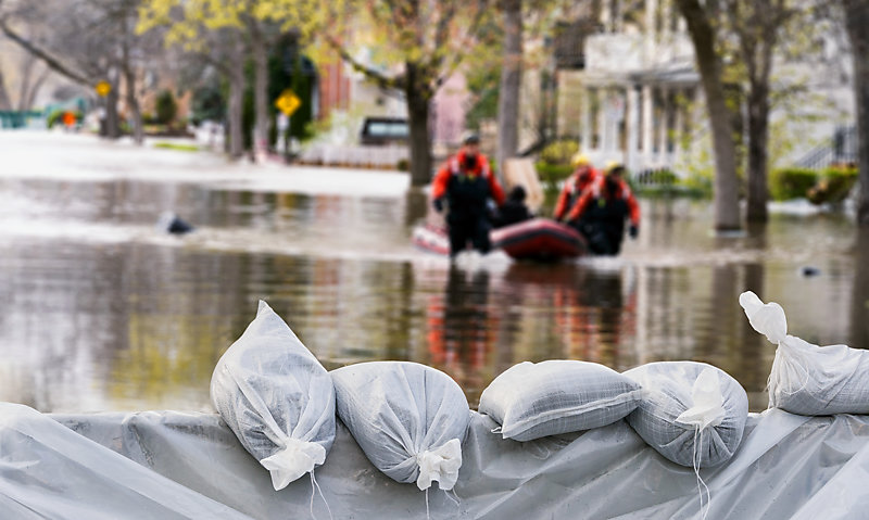 Sandbags used as flood protection, with flooded homes in the background.