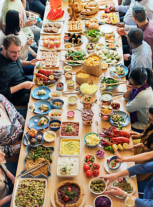 Many people around a table, eating at a Cuisine Buffet Party Concept.