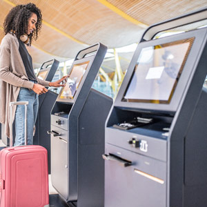 Woman using the check-in machine at the airport, getting the boarding pass.