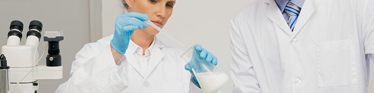 Two scientists analyzing milk in a beaker.