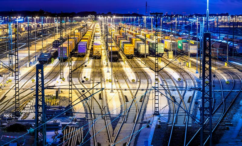 Freight train cars stationed on multiple rows at an industrial docking station by night.