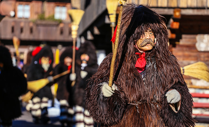 Carnival parade with bear-like man in the foreground wearing a fur coat with a hood and a mask.