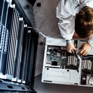 An IT engineer servicing parts of a computer.
