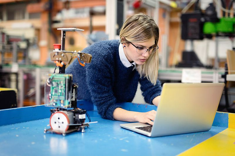 A young woman engineer working on a robotics project.