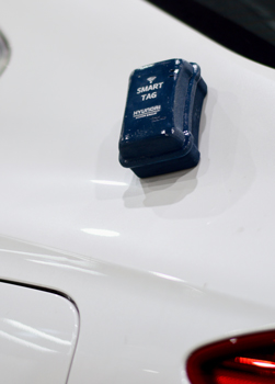Smart tag device fixed on the bonnet of a white car.