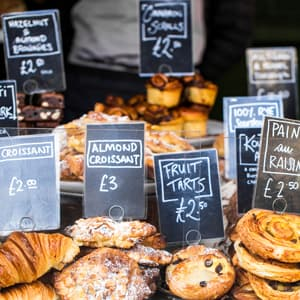 Close up color image depicting a large selection of artisan gourmet breads and pastries displayed on a bakery stall at Borough Market, London, UK, one of the most popular and oldest food markets in the world. Each item is labelled and priced. Room for copy space.