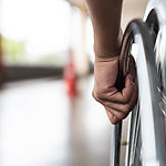 Close-up of a disabled man's hand, holding the wheel of his wheelchair.