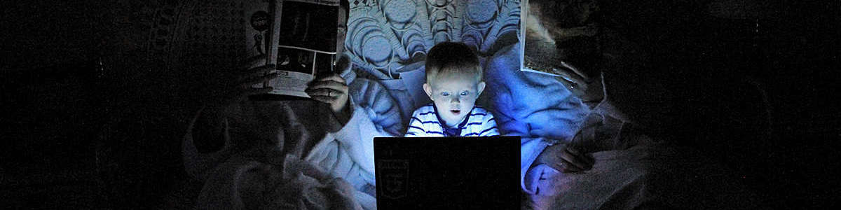 A little boy stares at a laptop screen while his parents are reading.