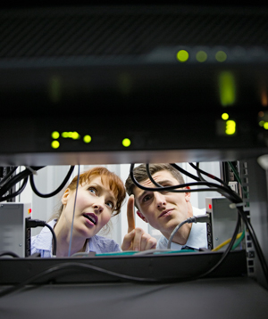Two technicians talking and looking at a server.