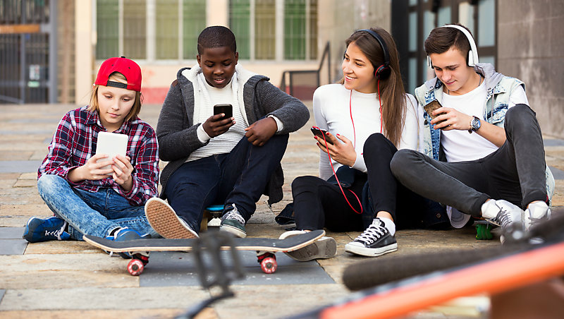 Teenagers sitting on the ground with eyes on their mobile phones.