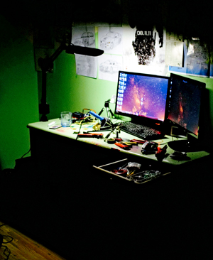 Desk lamps shines on two screens in a dark room.