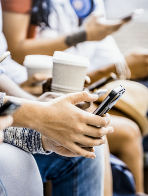 Close-up of people's hands using smartphones and holding paper coffee cups.
