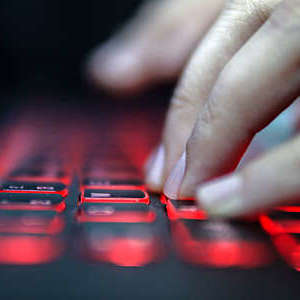 Close up of the hands of a woman typing on a red lit laptop keyboard.
