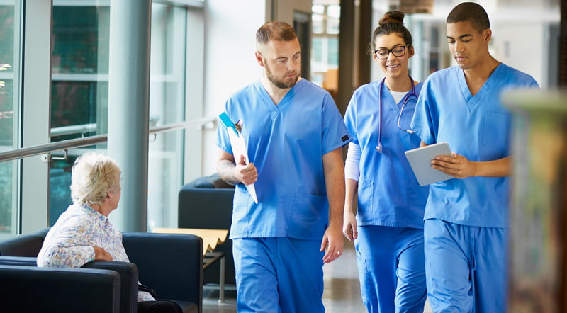 Three junior doctors wearing blue scrubs walk down a hospital corridor discussing a patient's medical case.