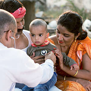 Paediatrician examines a sick baby boy during a home visit in a village.