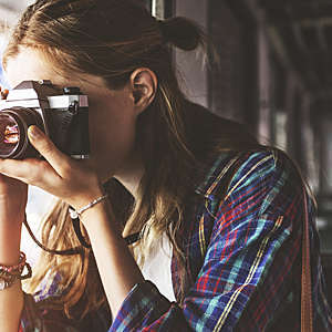Close-up of girl taking a picture.