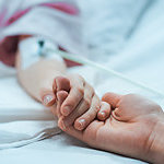 Close up on the holding hands of a mother and her recovering child, lying in a hospital bed.