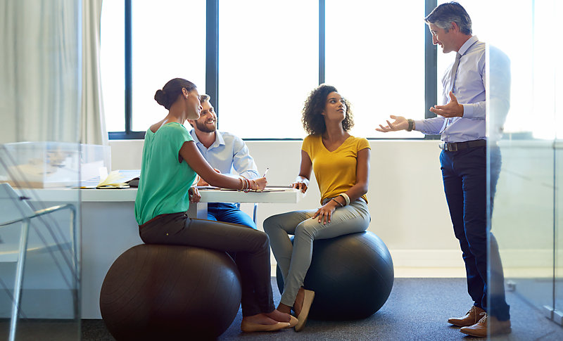 People in a meeting, two of them sitting on an exercise ball rather than a regular office chair.