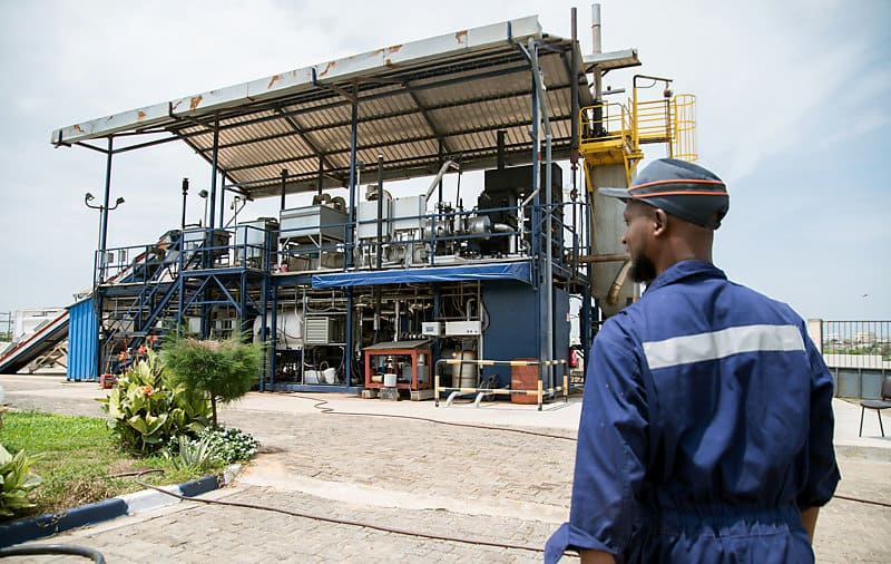 Janicki Omni Processor waste treatment plant in Dakar with worker in blue overalls standing in the foreground.