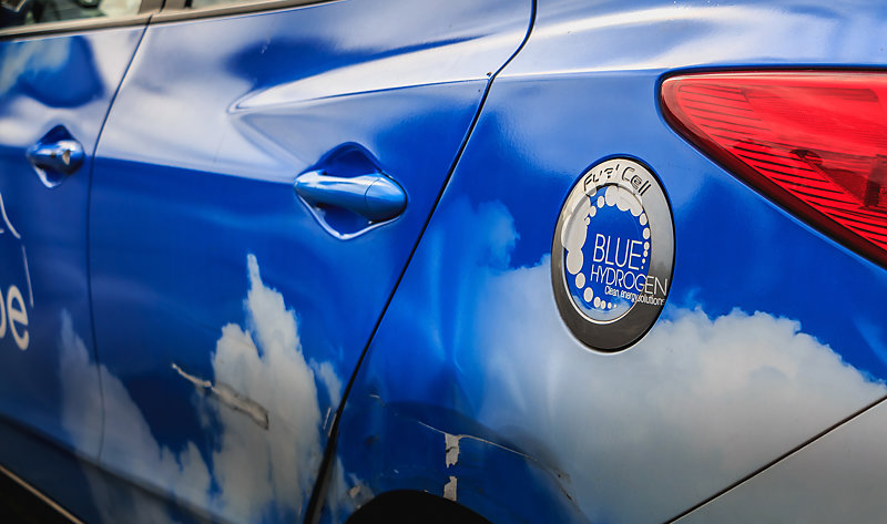 Close-up of logo on the blue bodywork of a hydrogen-powered taxi.