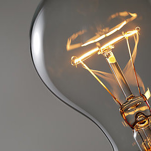 Close-up of a light bulb with its filament glowing.