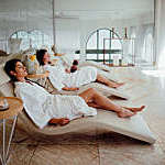 Two women in white robes relaxing at hotel spa.