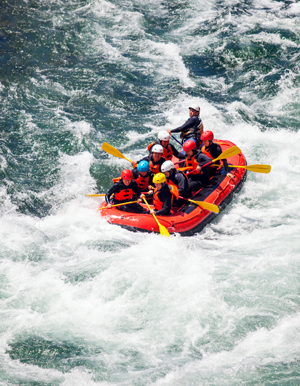 Group of men and women rafting on a river.