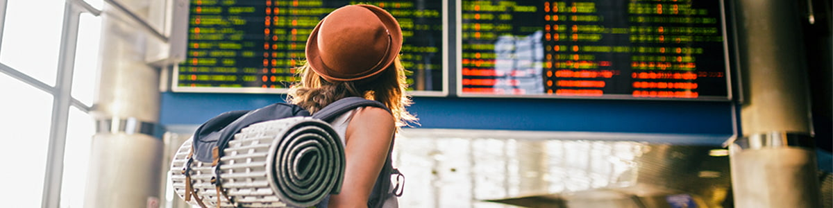 Woman with a backpack and camping equipment looking at the schedules on the scoreboard airport station.