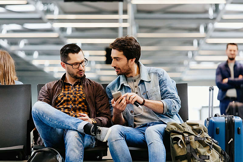 Two young men sitting at an airport lounge using a mobile phone.