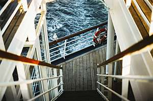 Flight of stairs descending towards guard rail of cruise ship with gull perched on top and ocean visible in background.