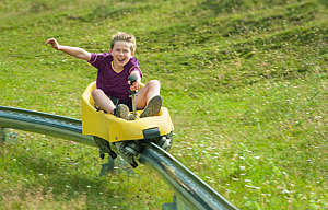 Boy going downhill at summer toboggan run - stock photo